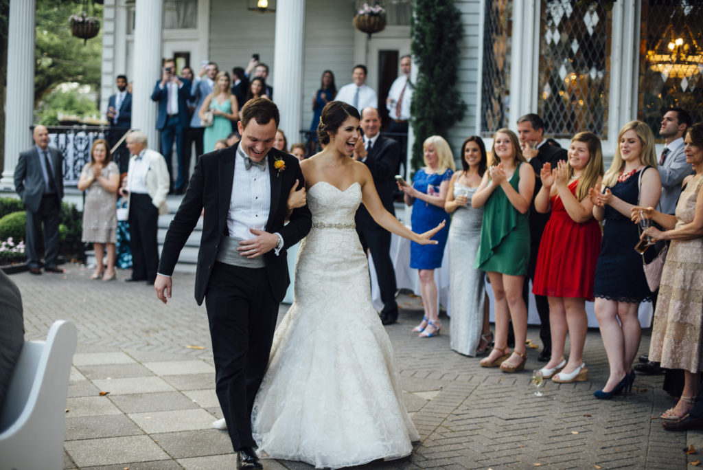 Founders of WedTexts, Caleb and Kelly White walk through a crowd on their wedding day