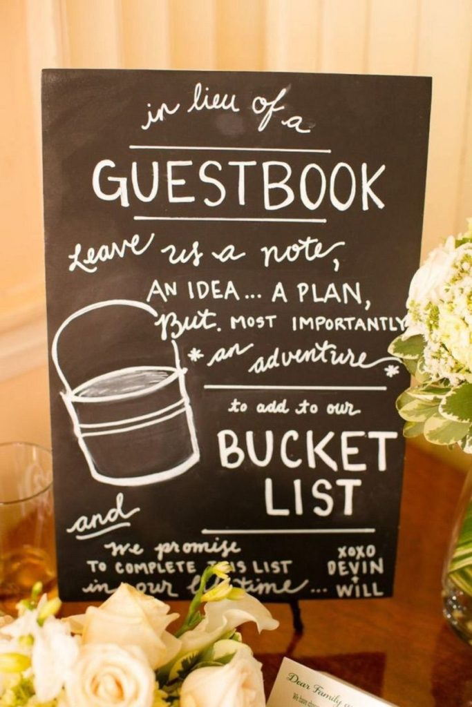 "Chalk sign that reads, ""in lieu of a guestbook leave us a note, an idea... a plan, but, most importantly an adventure to add to our bucket list."""
