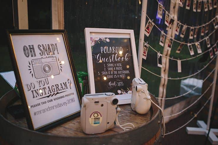 Poloroid cameras on a barrel with signs explaining to use them in place of the wedding guest book